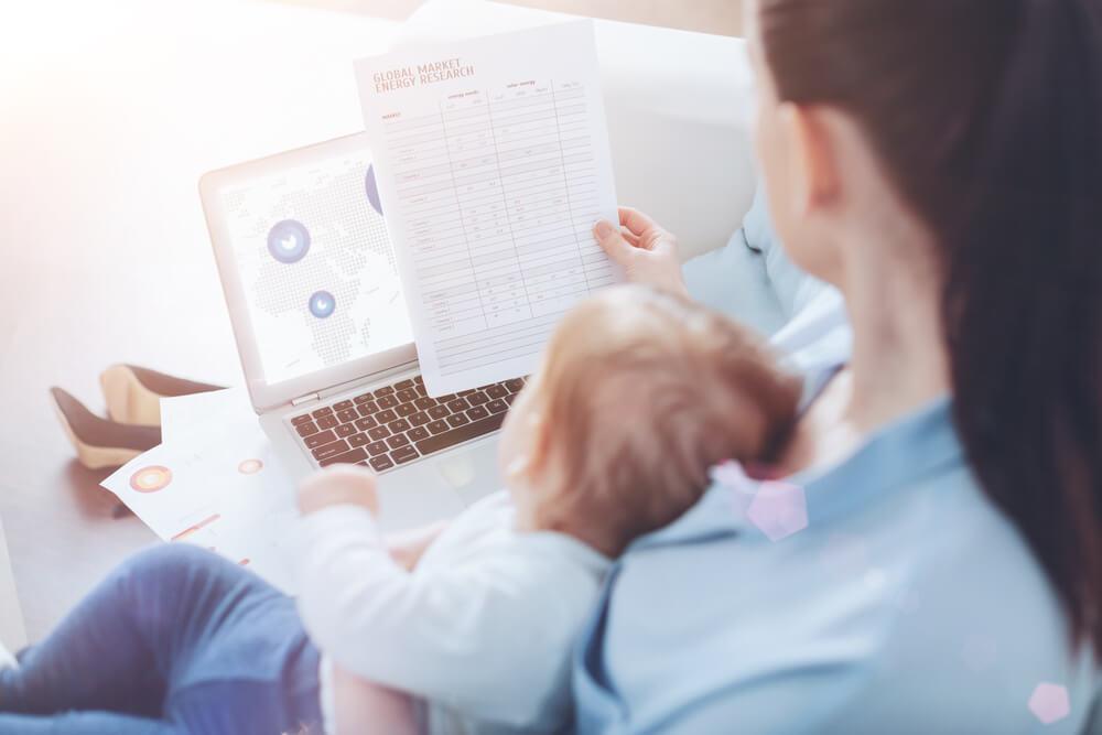 женщина с младенцем за работой в ноутбуке